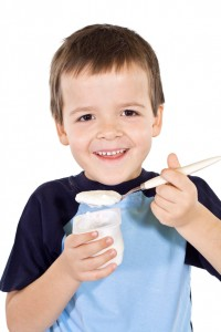 Healthy happy boy eating yogurt - isolated